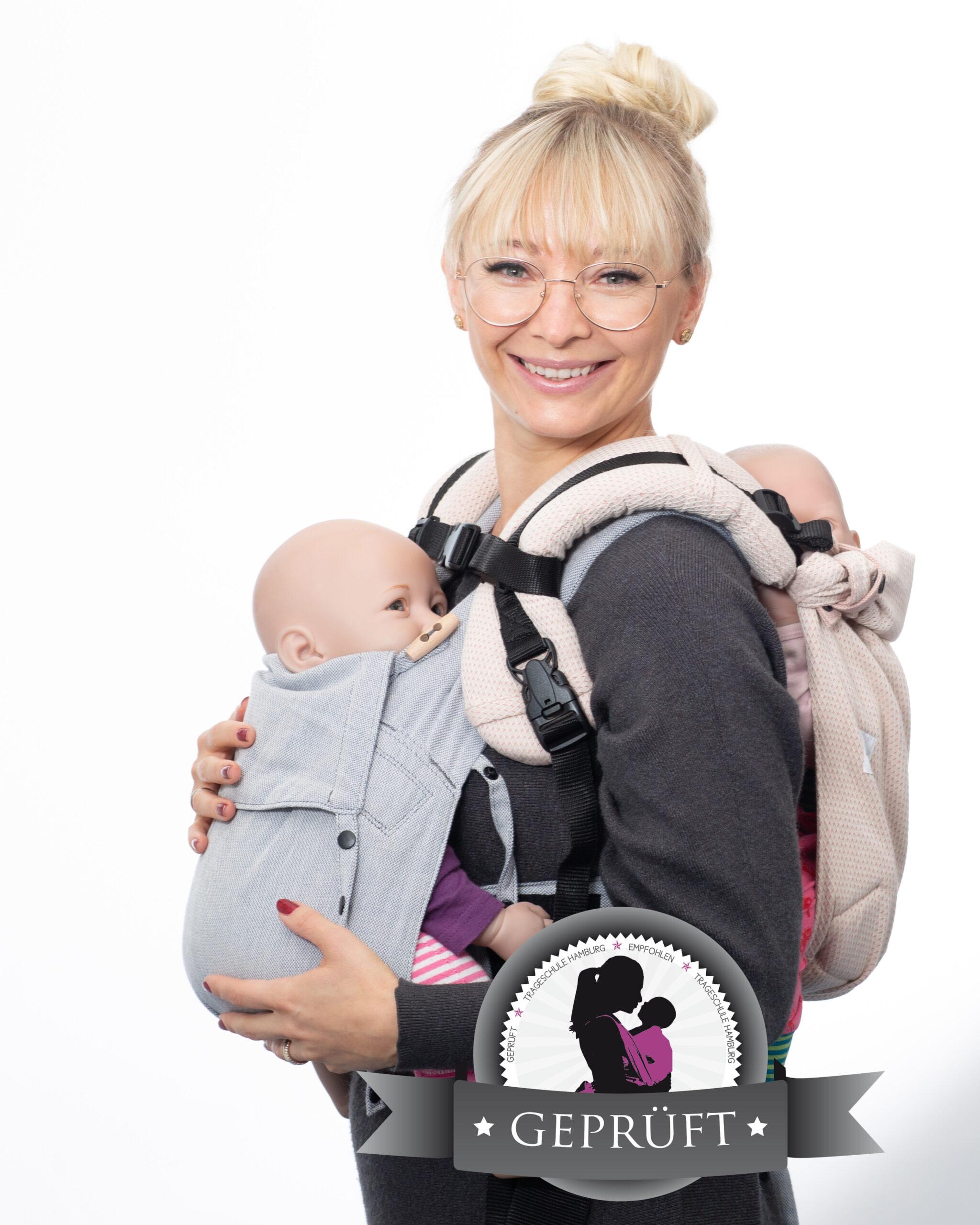 Frau mit zwei Babys in der Tragehilfe